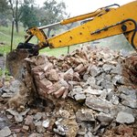 An excavator removes debris from a demolition site.