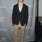 Justin Long dressed in khakis and a pair of oxfords.