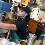 Starbucks staff readies a drink for a customer