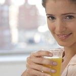 Woman holding glass of orange juice.