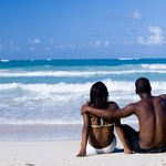 Dominican couple sitting at the beach