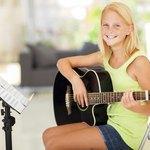 Girl holding guitar next to sheet music