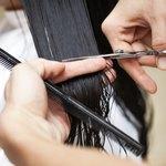stylist cutting woman's hair in salon