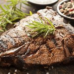 Grilled steak seasoned with salt, pepper, and rosemary