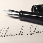 Fountain tip pen lying on greeting card with the words