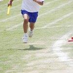 A teenaged boy running in a relay race.