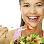 Lifestyle photo of woman smiling and eating salad.