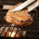 Moving steak on grill with tongs.