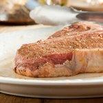 Raw T-Bone steak on plate.