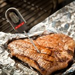 Meat thermometer in a grilled steak.