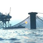 Covered salmon cage near an oil rig