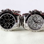A pair of stainless steel Rolex Daytona watches.