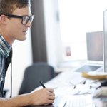 Man sitting behind computer at desk