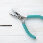 Squeeze the handles of the pliers together to cut the wire