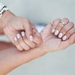 A subtle mini moons manicure mixes nude and wide.