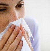 A woman blows her nose into a tissue.