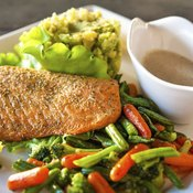 Grilled piece of salmon on dinner plate.