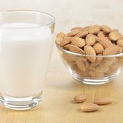 A glass of almond milk and a bowl of almonds.