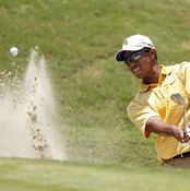Tiger Woods uses a sand wedge to escape from a bunker.