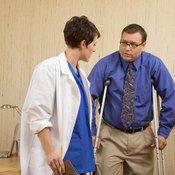 Doctor treating man's ankle sprain