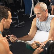A trainer is helping this older man with preacher curls.