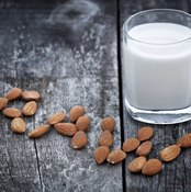 A glass of almond milk with almonds.