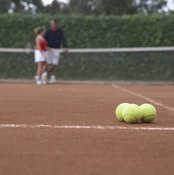 A tennis court includes the area within the fencing or other boundaries