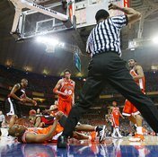 A referee calls for the clock to stop due to a foul.