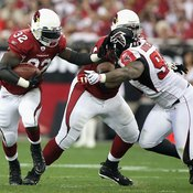 With the blocker angling his defender to the left, Cardinals running back Edgerrin James cuts to his right in a 2009 NFC playoff contest.