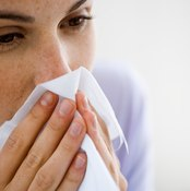 Woman coughing into tissue