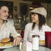 A couple is eating out at a burger joint.