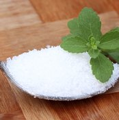 Close-up of a spoonful of stevia powder, with a stevia leaf on top.