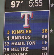 Baseball lineups on scoreboards show abbreviations for each player's position.