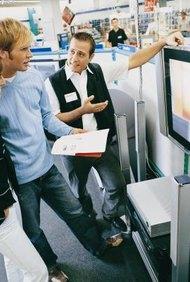 El personal de ventas en planta le explica al cliente las características del producto y las garantías.