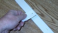 Here's a nail pushed through the piece of paper. Once the nail is driven in, simply pull out the  paper.