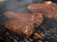 A porterhouse steak sizzling on a grill.