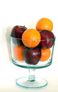 A glass pedestal bowl filled with apples and oranges.