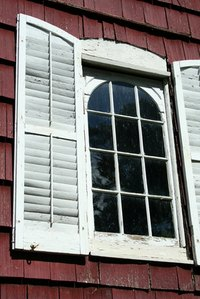 Wooden shutters with peeling paint.