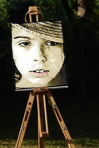 Display a decoupaged color photocopy on canvas on an easel.