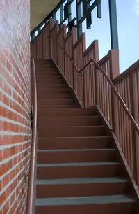 Exterior stairs along a brick wall.