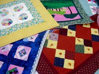 Quilts with tacking have knots with long tails to add dimension and texture, as on this red quilt's yellow diamonds.