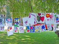 Art painted by kids, hanging on a line to dry.