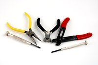 Pliers or wire cutters can be used to cut a coat hanger.
