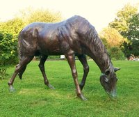 Make a stand of grass or hay out of paper mache to help support the long, fragile legs of the horse statue.