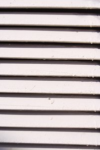 The slats of a jalousie window are operated by a crank.