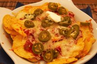 Cheese dip poured over tortilla chips makes delicious nachos.
