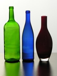 Empty glass bottles can be used to make art when broken into smaller pieces.