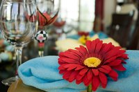 A traditional rolled napkin with a flower napkin ring spices up a table setting.