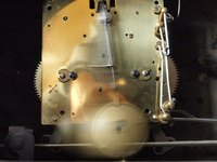 Pendulum clock with pendulum in motion.