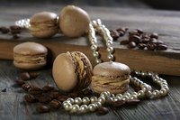 An elegant still life of coffeebeans, almond cakes and a string of pearls on wood.